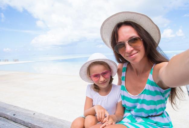 Moeder en meisje die selfie bij tropisch strand nemen