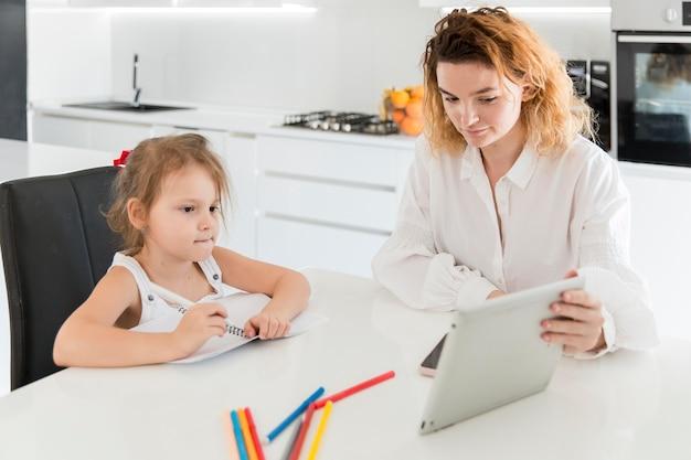 Moeder en meisje die tablet bekijken