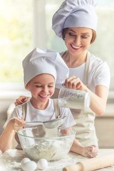 Moeder en meisje glimlachen terwijl het deeg wordt voorbereid