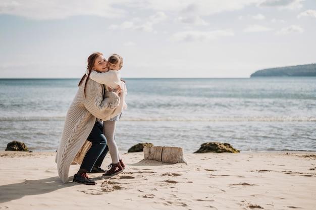 Moeder en meisje knuffelen op strand