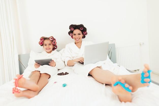 Moeder en meisje liggen op het bed en kijken naar de camera.
