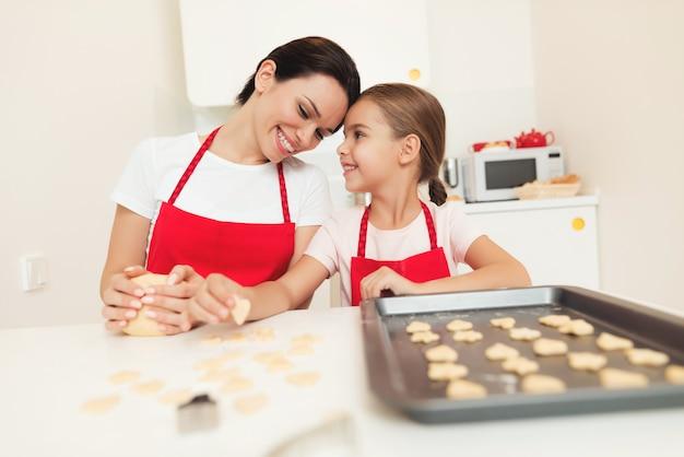 Moeder en meisje maken koekjes in de keuken.
