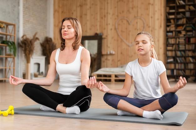 Moeder en meisje mediteren op yoga mat