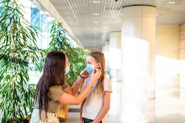 Moeder en meisje met medische maskers op de luchthaven. bescherming tegen coronavirus