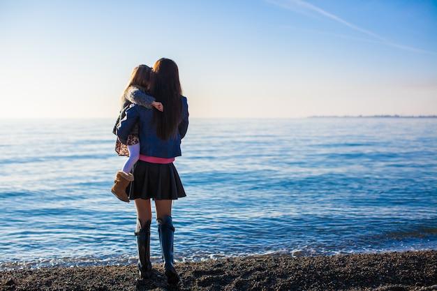 Moeder en meisje op strand in zonnige de winterdag