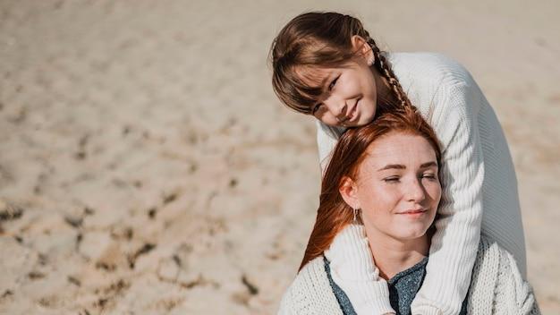 Moeder en meisje poseren op strand