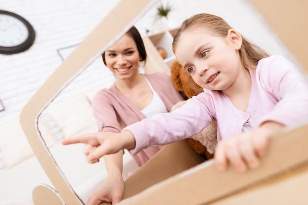 Moeder en meisje spelen auto gemaakt karton thuis.