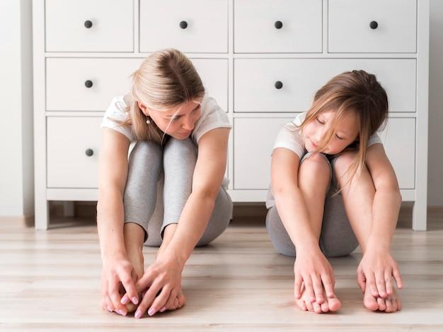 Moeder en meisje strekken zich uit