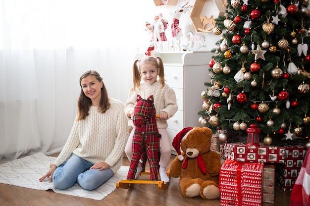 Moeder en meisje thuis in de buurt van kerstboom en geschenkdozen