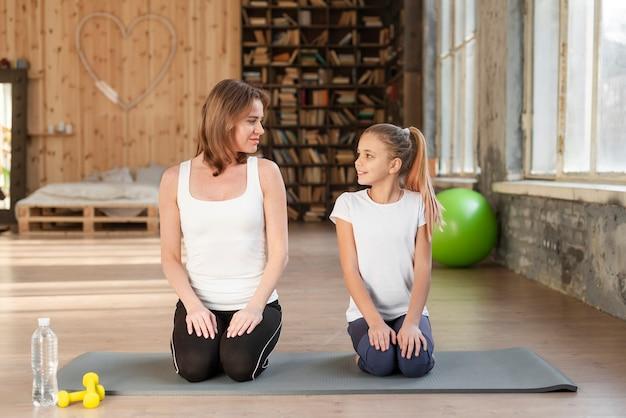 Moeder en meisje, zittend op yoga mat