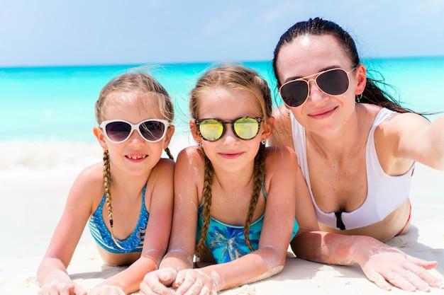 Moeder en meisjes die selfie bij strand nemen die op wit zand liggen. de gelukkige familie neemt selportrait ontspannend op vakantie