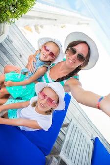 Moeder en meisjes die selfie bij tropisch strand nemen
