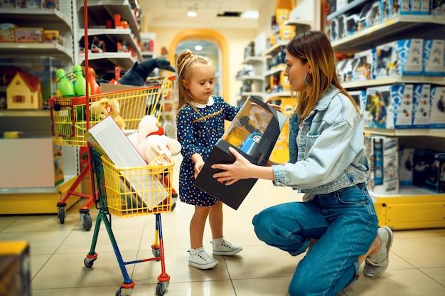 Moeder en mooie kleine baby die speelgoed in opslag kopen