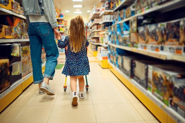 Moeder en mooie kleine baby in speelgoedwinkel