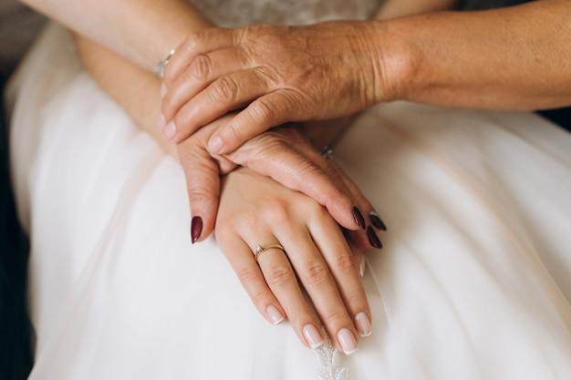 Moeder en oma houdt de hand van de bruid vast