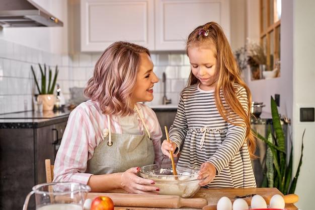 Moeder en schattige dochter samen koken in de keuken, mooie moeder leert schattige jongen meisje deeg kneden voor binnenlandse taart verrassing voorbereiden voor familie