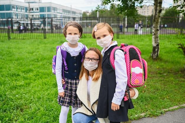 Moeder en schattige dochters met gezichtsmasker voor veiligheidsbescherming. schoolmeisjes klaar voor school.