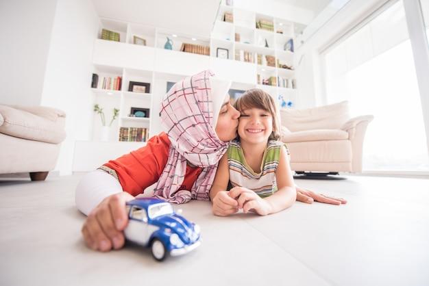 Moeder en schattige zoon spelen met auto speelgoed in de woonkamer