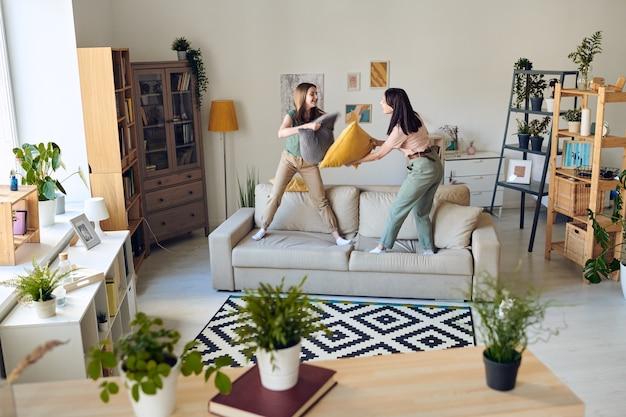 Moeder en tienerdochter die zich op bank bevinden en hoofdkussengevecht hebben in de woonkamer