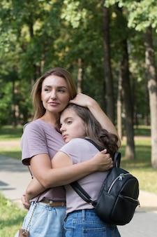 Moeder en tienerdochter hebben plezier tijdens een wandeling in het park. gelukkig familieconcept