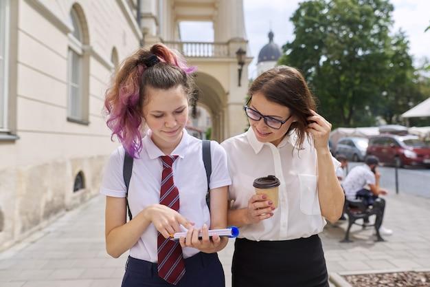 Moeder en tienerdochter lopen samen op straat in de stad. pratende moeder en studente, ouder en kind bespreken school, studie