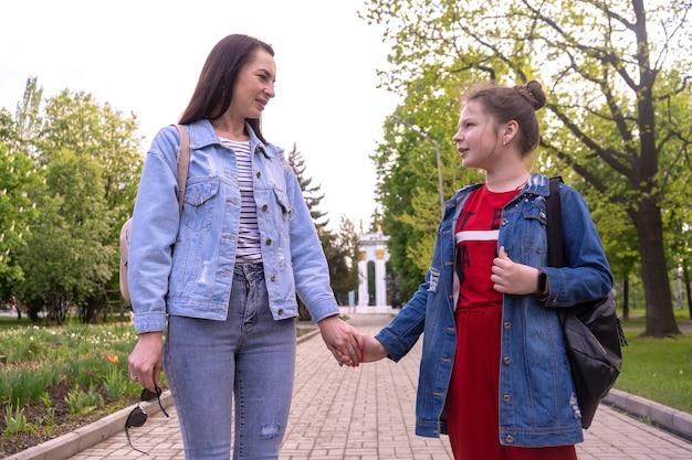 Moeder en tienerdochter wandelen in een park, hand in hand, gelukkige jonge blanke vrouw met lang haar en tienermeisje hangen in een stad, lifestyle-familie