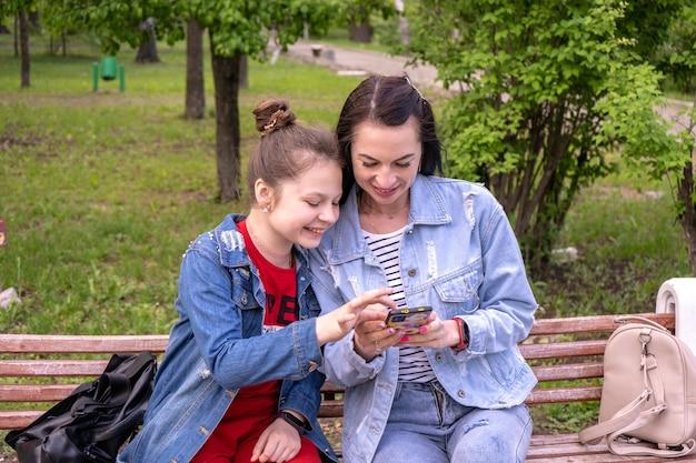 Moeder en tienerdochter wandelen in een park, zittend op een bankje en kijken in smartphone, gelukkige jonge blanke vrouw met lang haar en tienermeisje surfen op internet buitenshuis, lifestyle familie