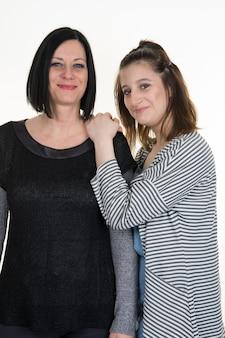 Moeder en tienerdochterportret op wit wordt geïsoleerd dat