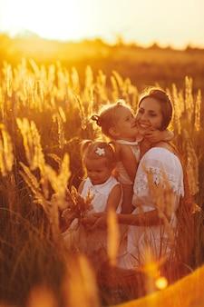 Moeder en twee dochters hand in hand cirkelen. familie tijd samen bij zonsondergang. vrolijke picknick. zachte focus.