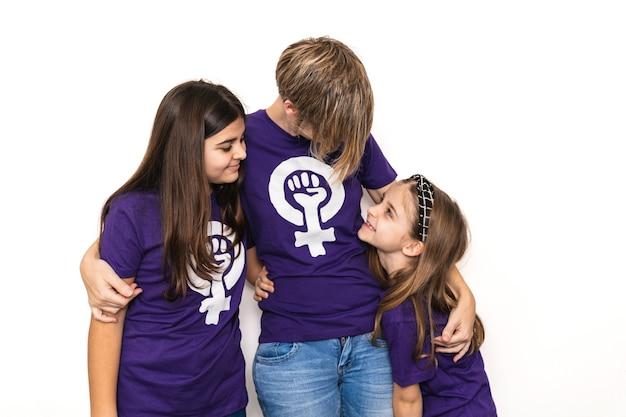 Moeder en twee dochters omarmen met paars t-shirt met het symbool van de internationale feministische vrouwendag op een witte muur