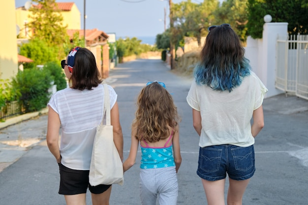 Moeder en twee dochters tiener en jongste lopen samen hand in hand