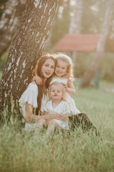 Moeder en twee dochters wervelden. moeder houdt dochters op handen. familie tijd samen. een prachtig portret van moeder met twee dochters in het park