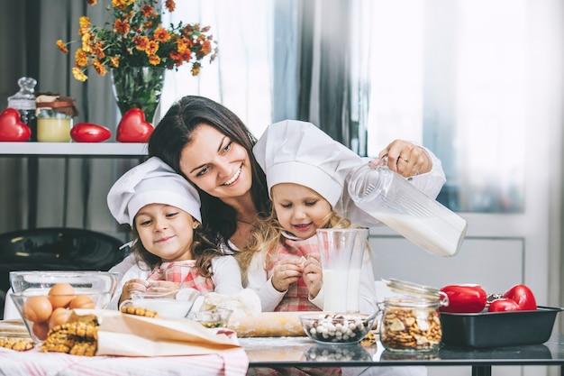 Moeder en twee gelukkige kleine babymeisjes consumptiemelk en koken aan de tafel in de keuken is mooi en mooi