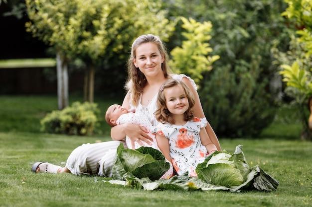 Moeder en twee kinderen, babymeisje en dochtertje op het gras met kool op zomerdag