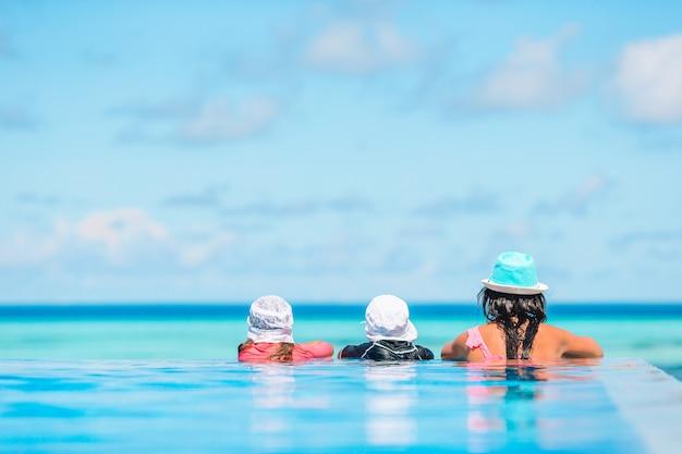 Moeder en twee kinderen genieten van zomervakantie in luxe zwembad