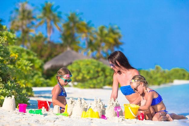 Moeder en twee kinderen spelen met zand op tropisch strand