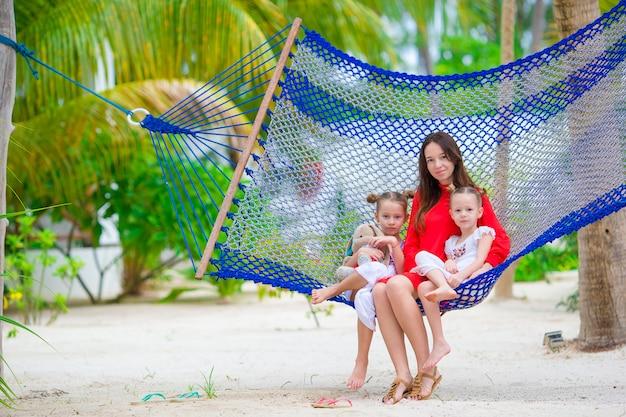 Moeder en twee kinderen zitten op hangmat op tropisch strand