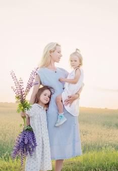 Moeder en twee kleine dochters voor een wandeling in het veld bij zonsondergang