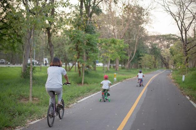 Moeder en twee zoon fietsen op fietsstrook.