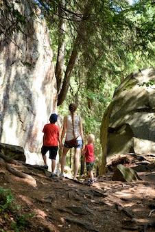 Moeder en twee zoontjes staan bij de rotsen in het bos. vrije tijd