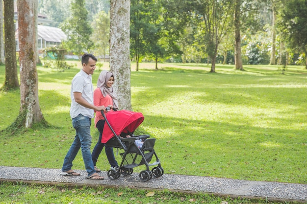 Moeder en vader duwende kinderwagen in park