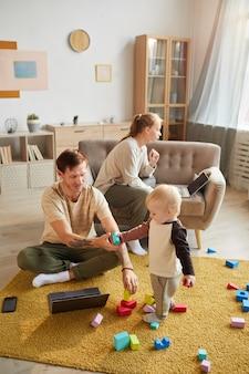 Moeder en vader gebruiken hun computers en werken thuis terwijl hun kind met speelgoed speelt
