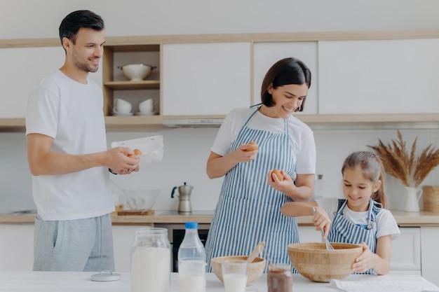 Moeder en vader geven eieren aan dochter die deeg bereidt, bezig is samen te koken tijdens het weekend, gelukkige buien heeft, eten klaarmaakt. drie familieleden thuis. ouderschap en samenhorigheid concept