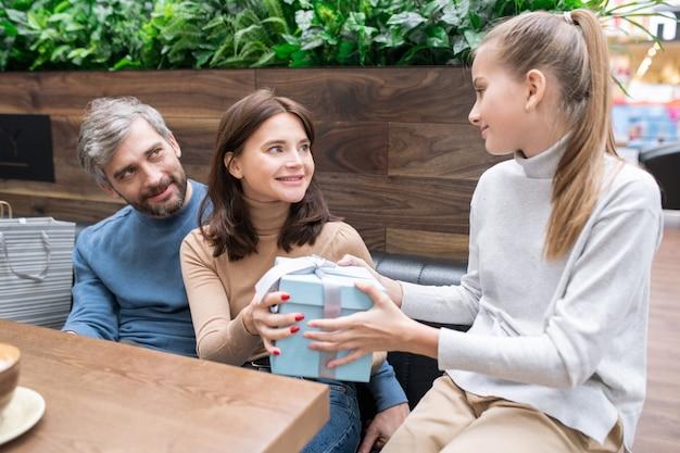 Moeder en vader geven verpakte blauwe geschenkdoos door aan hun dochter terwijl ze haar gelukkige verjaardag wensen tijdens de rust in het café