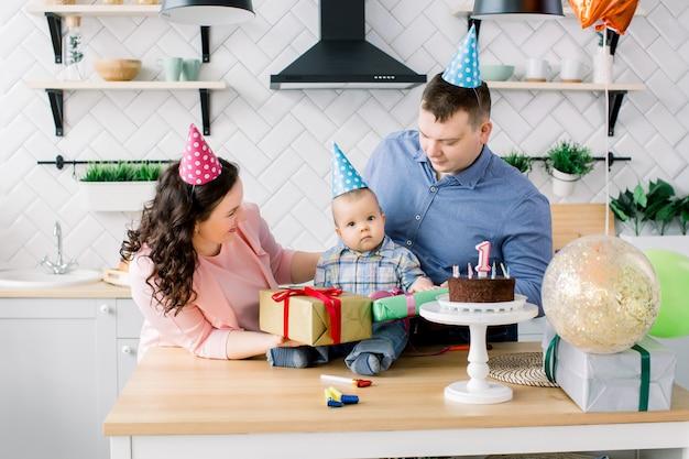 Moeder en vader in verjaardag hoeden vieren eerste verjaardag van babyjongen thuis keuken. gelukkige familie viert verjaardag met een taart, huidige dozen, feesthoorns en ballonnen