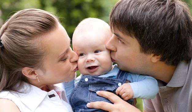 Moeder en vader kussen hun kleine peuter