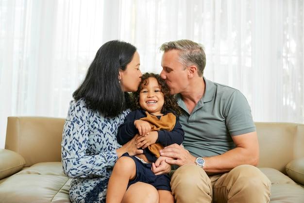 Moeder en vader kussen hun schattige gelukkige zoontje op beide wangen als ze thuis op de bank zitten