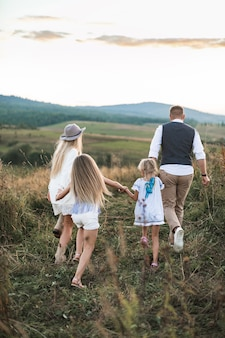 Moeder en vader spelen met hun kinderen dochters in het veld