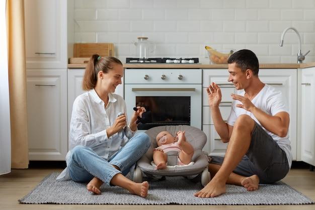 Moeder en vader spelen met zoon of dochter in schommelstoel op lichte kamervloer met keuken op achtergrond, gelukkige familie tijd samen doorbrengend, spelend met baby.