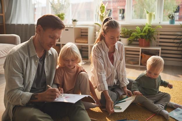 Moeder en vader tekenen samen met hun twee zoontjes op de vloer in de woonkamer